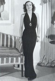 """""""Joan Crawford in No More Ladies (1935) is dressed in a signature sleek and timeless dress by Adrian. The halter neck style was now important for eveningwear, and designer Madeleine Vionnet promoted the look. In the Thirties, costume jewellery was worn big and bold in the evening, in contrast with the demure, tailored looks and simple dresses for day."""""""