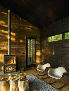 A Rustic-Modern Cabin Inspired by Japanese Bungalows and Shou Sugi Ban - Photo 1 of 12 - A little cottage in North Carolina is furnished with a cluster of wood-stump end tables by Urbia,  two Eames rockers, and a 16-H wood-burning stove by Stûv.