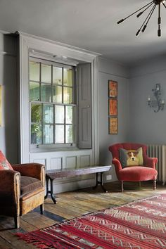 Hall with interior window in Hallway Design Ideas. Large light grey room with stripped wooden floor boards, antique armchairs, wooden bench and red kilim rug.