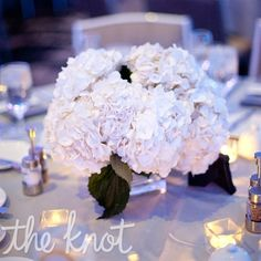 "cream hydrangeas in a square vase with small square votives for the ""small"" centerpieces. Surrounded by pillar candles of staggered heights for the ""medium"" centerpieces."