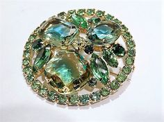 ITEM # 121643  Beautiful verified DeLizza & Elster aka Juliana givre art glass rhinestone brooch.  The focal point of this brooch is obviously the three large faceted givre art glass rhinestones in shades of green blue and yellow all open back, there is a center yellow round faceted foil back in the center with 4 green foil back navettes and 6 foil back rounds scattered inside the brooch. There are 32 small round faceted foil back accent rhinestones running the circular border, for a tota...