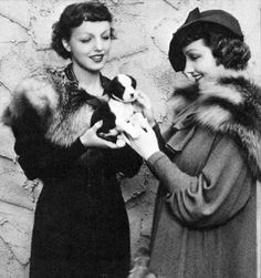 "Claudette Colbert giving her stand-in, Pluma Noisom, a prize bull terrier puppy in appreciation for her work on the 1935 movie ""She Married Her Boss"""