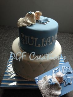 2 Tier baptism cake with edible hand crafted baby as a topper sleeping on a blue and white cross.
