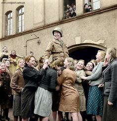 Ukrainian girls who had to work as forced laborers in Germany joyfully cheering an American soldier. -