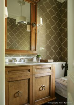 GREENWICH, CT | VALERIE GRANT INTERIORS - Powder room with light wood vanity and mirror. Bathroom sconces flank the wood framed mirror. Neutral color wall paper adds a subtle elegance. #powderroom #woodvanity #wallsconces #wallpaper