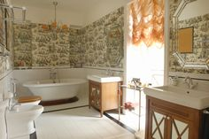 Bathroom in white and vibrant wallpaper. Two separate vanities framing large window.  Free standing tub at one end and toilet situated in the center against the wall opposite the vanities and window
