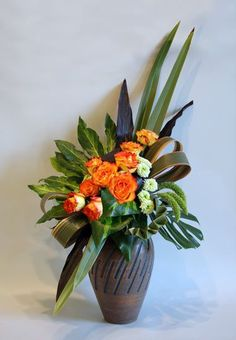 Circus roses, button mums, green millet, phormium, red ti and aralia leaves, monstera leaf