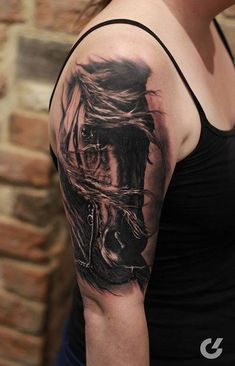 Black and grey horse tattoo on the right upper arm.
