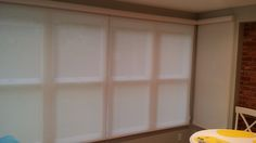 Roller shades installed closely together. Shades have casement head rail that holds the shade when raised. Call us at 419-381-2700