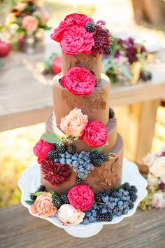 Tiered Chocolate wedding cake with flowers and fruit.