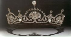 One of the prettiest of Queen Elizabeth''s (QEQM) tiaras, which she has now given to Princess Margaret, was Egyptian in inspiration, arranged as a band of stylized lotus flowers and overreaching arches, with the graduated pinnacles surmounted by a single pearl.