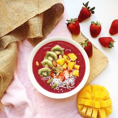 Berry smoothie bowl topped with kiwi fruit, mango, strawberries, coconut