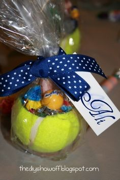 Hollowed out tennis ball with candy, wrapped in cello and tied with a ribbon.