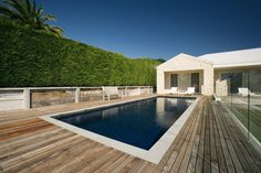 Aloha Pools Pty Ltd custom constructed this formal pool in Portsea, Victoria, Australia. Minimally treated timber and the striking green of an established hedge create amazing textural contrast around this idyllic, simple rectangular pool.