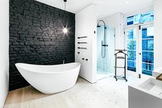 Primrose Hill House- love the black painted brick behind the bath. Would hate having to lean over to get to the taps when the bath starts to get cold though.