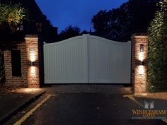 Accoya Wood Swing Gate How beautiful does this new installation in Camberley, Surrey look all lit up at night. Flemish bond brickwork to match the house with built in parcel box and slate name sign. Front Gate Design, House Gate Design, Fence Design, Timber Gates, Wooden Gates, Wooden Driveway Gates, Driveway Entrance, Driveway Lighting, Front Gates
