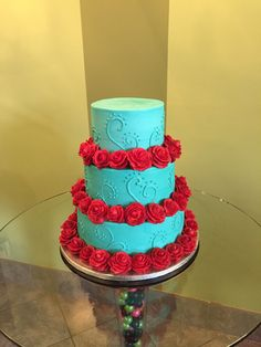 Dia de los Muertos inspired wedding cake. Teal buttercream frosted tiers with scroll work, accented by red buttercream roses. Add the sugar skull toppers and voila!