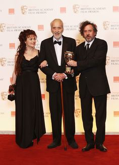 Tim Burton Photos Photos - Sir Christopher Lee, winner of the Academy Fellowship, poses in the press room with Helena Bonham Carter and Tim Burton during the 2011 Orange British Academy Film Awards at The Royal Opera House on February 13, 2011 in London, England. - Orange British Academy Film Awards - Winners Boards