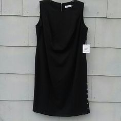 Calvin Klein Woman Black Sleeveless Sheath Dress Classic black sheath dress by Calvin Klein.  Silver zip back closure.  Silver snap side slit - just the bottom 3 buttons open and close.  Lovely silhouette!  Fully lined.  Poly, rayon, spandex blend. NWT Calvin Klein Dresses Midi