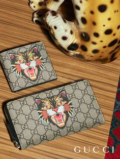 Up close with GG wallets from the Gucci Pre-Fall 2017 collection by Alessandro Michele, embellished by the Angry Cat print.