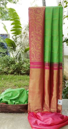 This shamrock green kanchivaram silk is chequered with gold zari. The border and pallu have different pattern in hot pink intricately woven with gold zari giving it an alluring charm