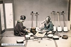1890's. A craftsman, wearing a traditional chonmage hairstyle, is working on a Shamisen, a three-stringed musical instrument played with a Bachi (plectrum), while being assisted by a woman in kimono. In the back five shamisen rest against the wall.