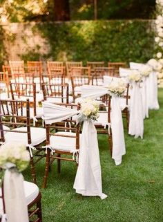 Chivari Chairs Draped In White Fabric tied with a nosegay of flowers, Great if you don't want to invest in chair ties for every single ceremony chair...and creates a beautiful aisle!