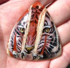 Angry tiger is on red jasper pendant.