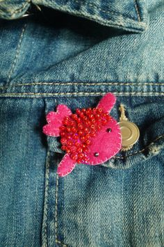 Handmade pink goldfish brooch decorated with hand sewn glass beads.