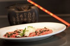 BEEF CARPACCIO WITH WHITE TRUFFLE OIL, CHILI OIL,CAPERS AND PECORINO ROMANO