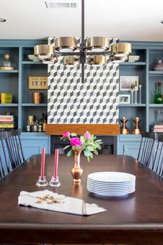 An industrial chandelier illuminates this simple dining room table and offsets the soft, feminine touches underneath.