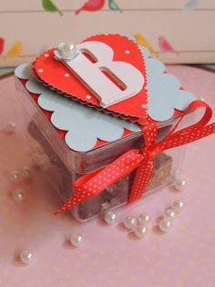 Caixa de acrílico personalizado com papel de scrapbook.  Inicial da criança, detalhe da flor e fita de cetim poá.  Não vai com chocolate, apenas ilustrativo.