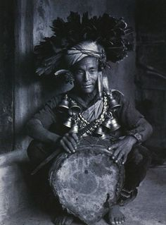 The Magar shaman Beth Bahadur sitting on the porch of a client's house. His drum has been fed with the blood of a sacrifical goat, evident from the bloodstains on the membrane.