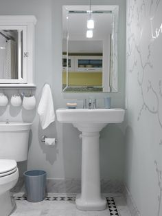 In this bright and cheery basement bathroom, designed by Sarah Richardson, a classic pedestal sink creates the illusion of extra square footage while a bright-white palette keeps the teeny-tiny space from feeling cramped.