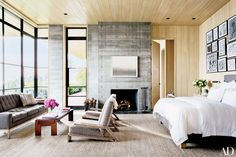 Elegant, neutral bedroom with lounge area, stone fireplace, and small wood coffee table