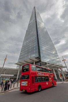 Typical red London bus stopping at the base of the Shard building in London, western Europe's tallest building