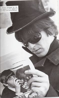 George reading a newspaper with Ringo on the back