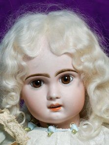 """FRENCH BISQUE BEBE BY JUMEAU. Marks: 11. 23"""". Bisque socket head, brown paperweight eyes, painted lashes, feathered and brushstroked brows, pierced ears, open mouth, shaded and accented lips, pale blonde mohair wig, French wood and composition jointed body, delicate white lace frock"""