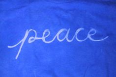 image of blue-dyed shirt with the word peace written in white using Elmer's Washable School Glue Gel