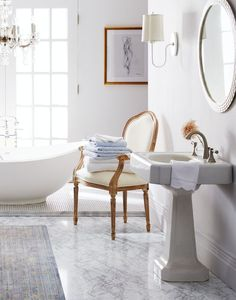 Love the mix of natural materials like linen and marble in polished finishes, paired with bright whites and gilded accents.