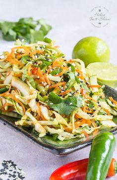An oblique shot of a green rectangular plate heaped with Asian coleslaw. Some chilis in the foreground, and an out of focus lime behind.