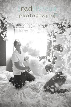 an adorable couple has a pillow fight in a bedroom. engagement shoot in burnaby bc, canada by award winning wedding photographer Kendra Coupland of Redivivus Photography.