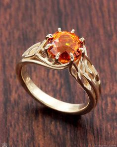 Embracing Tree Branch Engagement Ring with a beautiful orange sapphire solitaire. Customize this ring design in the metal and solitaire stone you want!