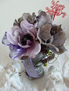 """アーティフィシャルフラワーのアネモネ、シルバー&パープル(各3輪)でアレンジ花系9cmの大輪の花がとても豪華ですアンティークグレーの花器が重厚感を…お花にたっぷりのラメ散りばめられているので、夜にはお部屋のライトでキラキラ光りとってもキレイです日頃の感謝をお花と共に届けて下さいね。""""母の日""""ピック付き花器の高さ:12cm仕上がり高さ:20cm・13Фアーティフィシャルフラワーを使用しています。水やり不要で枯れることなく永遠に"""