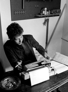 Bob Dylan using a typewriter and smoking a cigarette in his workroom over Café Espresso in Woodstock, 1964.
