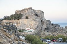 Parking lot with cars in Lindos city and mountain with the old and historic Castle , Rhodes Island, Greece. Europe.