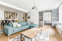 Avant/après : un 71 m2 parisien. Le salon à l'ambiance scandinave avec son canapé bleu et son parquet à chevrons