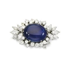 Sapphire and diamond clasp Of cluster design, set with an oval cabochon sapphire within a surround of brilliant-cut and marquise-shaped diamonds.