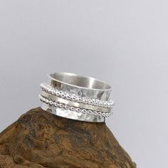 "Sterling silver spinner ring, meditation ring, with three outer spinning rings. I hand hammered the 10 mm (3/8"") flared band to give it dimension. Two of the spinner bands are 1.5 mm bead wire and the middle spinning band is a square wire with a brush finish. The three outer bands move"