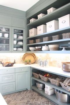 Grey and teal cabinets and brick floors